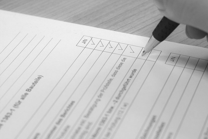 Person ticking off checklist on document